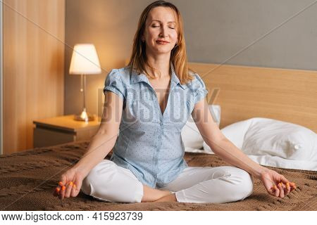 Portrait Of Smiling Peaceful Woman Relaxing On Lotus Position Sitting On Bed In Cozy Bedroom With Cl