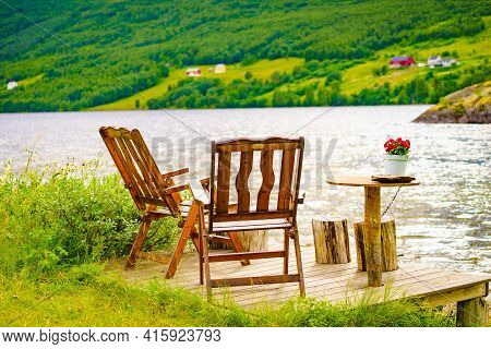 Picnic Site Rest Stop Area Wooden Table With Flowers Decoration And Chairs On Norwegian Lake Fjord S