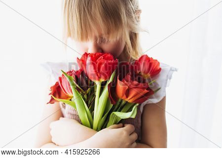 Small Smiling Girl Holding And Sniffing Bouquet Of Red Tulip Flowers. Concept For Greeting Card For