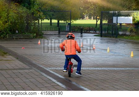 Rear View School Kid Learns To Ride A Bike In The Park, Outdoor Portrait Of A Young Boy Practicing H