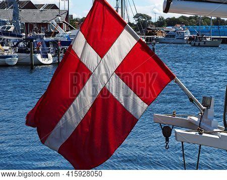 Flag Of Denmark Up High On A Sail Yacht In A Small Marina