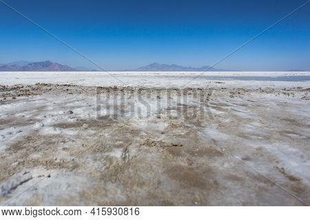 World famous Bonneville Salt Flats outside Salt Lake City Utah with mountains and blue skies. Detail of the salt on the ground