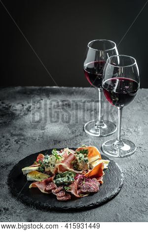 Antipasto Platter. Glass Of Red Wine With Various Cheeses And Prosciutto On A Black Background. Vert
