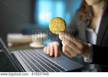Close Up Of A Businesswoman Hand Holding A Cookie In The Night At Homeoffice