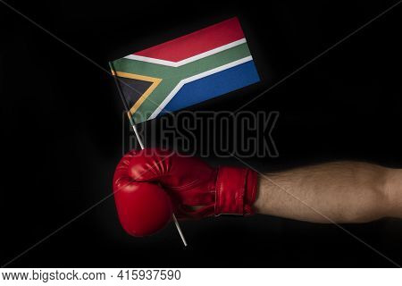 Boxer Hand Holds Flag Of South Africa. Boxing Glove With The South Africa Flag. Black Background