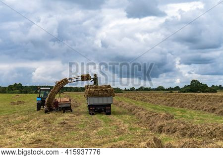 Russia, Kaliningrad Region, July 12, 2020. Combine For The Formation Of Hay Packages. Machine For Ha