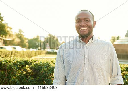 Happy Smiling Man Outdoors. Outdoor Portrait Of Smiling Young African Man On The Park