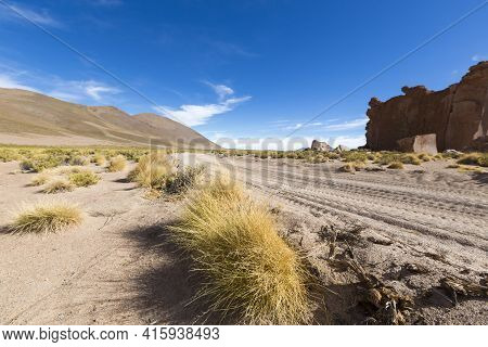 Sandy Track And Arid Landscape With Blue Sky In Bolivia