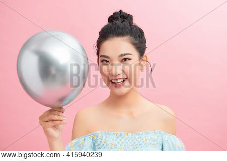 A Woman Holding Silver Balloon Against A Pink Background