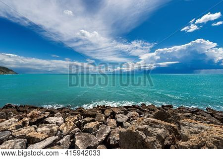 Rocky Beach And Beautiful Green Seascape With Storm Clouds On The Horizon In Front Of The Ancient Vi