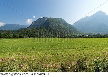 Valsugna Or Val Sugana. Summer Landscape Of Sugana Valley With Green Meadows And Mountains. Borgo Va