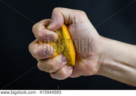 A Man Dramatically Squeezes An Orange On A Black Background, Close-up. The Concept Of Work Fatigue,