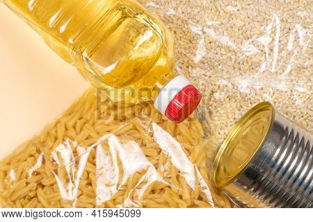 Paper Bag With Food Supplies Crisis Food Supply On A Light Yellow Background. Pearl Barley, Pasta, C