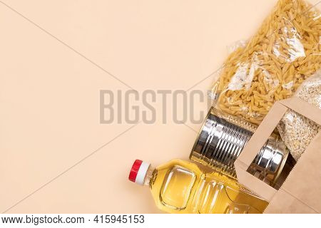 Paper Bag With Food Supplies Crisis Food Supply On A Light Yellow Background, Copy Space. Pasta, Can