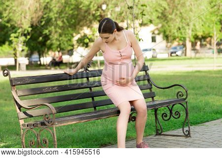 A Pregnant Young Woman On A Bench Sitting In The Park And Holds On To The Stomach Which Hurts. Pregn