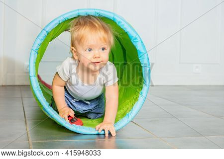 Toddler Blond Boy Crawl In The Tube With Toy Car