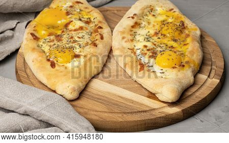 Baked Adjarian Khachapuri With Whole Egg Yolk On Wooden Board, Traditional Dish, Top View