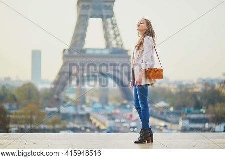 Young French Woman In Paris Near The Eiffel Tower. Beautiful Girl Walking In Paris, France. Tourist