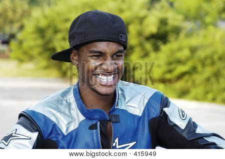 Biker Sits On Motorcycle Wearing Jacket And Hat Backwards Laughing Histerically