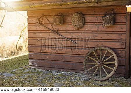 Old Peasant Tools Hanging On Wooden Wall On Animal Farm.