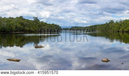 Flat River With Stones And Clouds Reflection In The Water, Venezuela