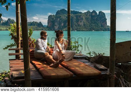 Beautiful Couple Relaxing On An Island Off The Coast.  Young Couple By The Sea. A Man And A Woman Tr
