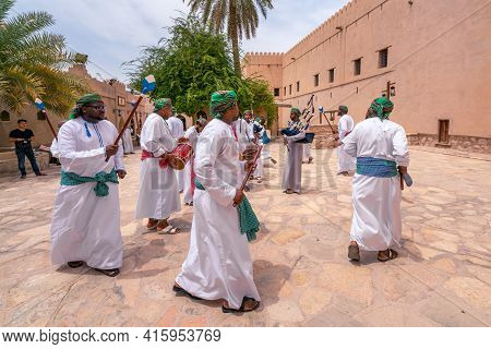 Nizwa, Oman - 04.06.2018: Men In Traditional Dress Playing Pipes, Singing And Dancing Around In A Ce