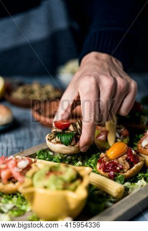 a young caucaisan man takes an appetizer from a wooden tray with some different vegan appetizers, with different toppings, placed on a gray rustic table