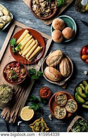 high angle view of a gray rustic wooden table full of some different vegan snacks, side dishes, dips such as guacamole or sweet potato sobrasada, and some other ingredients to prepare vegan sandwiches