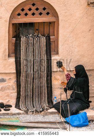 Nizwa, Oman - 04.06.2018: Woman In Tradiitonal Black Abaya Makes A Fabric In A Traditional Way. Trad