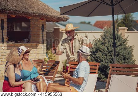 Group Of Senior Friends Relaxing And Sunbathing On Sun Beds By The Swimming Pool While On A Summer V