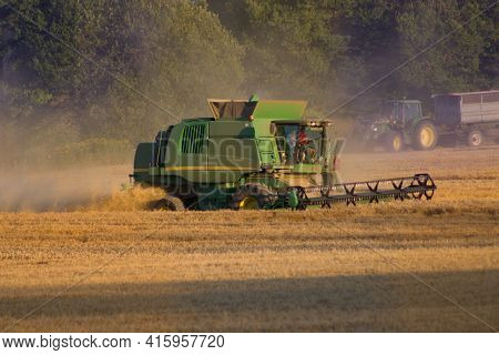 Combine Harvester Mows The Grain In The Field In The Early Evening.a Combine Harvester Or A Grain Ha