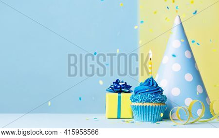 Birthday cupcake background with birthday gift, birthday party hat and falling confetti