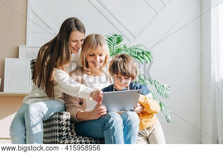 Family Mature Senior Woman With Adult Daughter And Child Kid Boy Using Digital Tablet Computer Devic