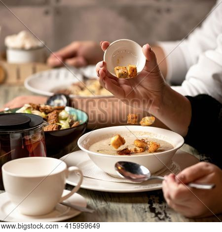Woman Adding Croutons To Bowl Of Mushroom Cream Soup On Table. Close Up Shot. Nutritious Wholesome F