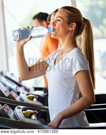 Happy Young Fit Woman Drinking During Workout, Running In The Gym