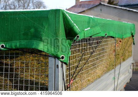 A Properly Covered Pile Of Cut Grass From Garden Maintenance On A Trailer With A Lattice Superstruct