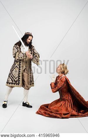 Full Length Of Cruel Hispanic King In Medieval Clothing Holding Sword Near Scared Queen In Crown Sit