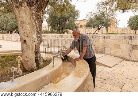 Jerusalem, Israel, March 23, 2021 : A Muslim Janitor Thoroughly Washes The Drinking Taps On The Temp