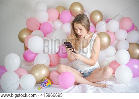 Surprised Young Lady Typing On Smartphone In Her Bedroom.surprised Young Lady Typing On Smartphone I