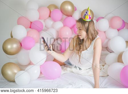 Photo Of Joyful Woman Smiling And Taking Selfie Photo On Cellphone  With Balloon. Birthday Party. Lo