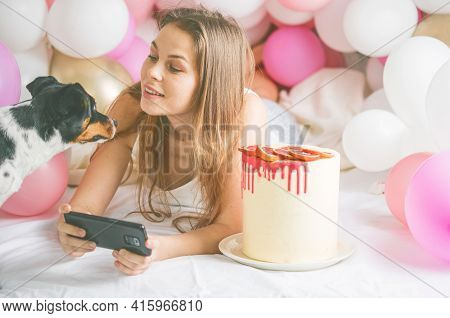 Lovely Lady In Pajama Making Selfie In Her Bedroom Using Phone And Play With Her Dog. Indoor Portrai