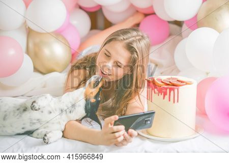 Lovely Lady In Pajama Making Selfie In Her Bedroom Using Phone And Kiss  Her Dog. Indoor Portrait  G