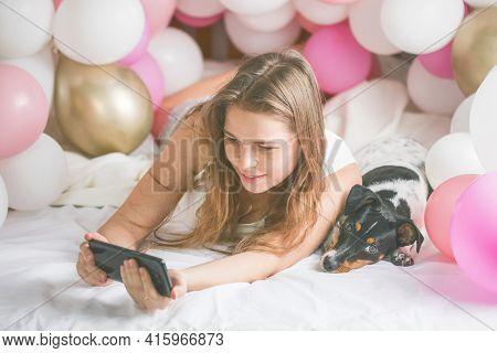 Lovely Lady In Pajama Making Selfie In Her Bedroom Using Phone And Hug Her Dog. Indoor Portrait  Gir