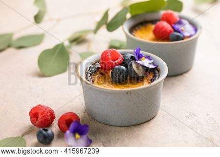 Creme Brulee. French Vanilla Cream Dessert With Caramelised Sugar And Berries, Selective Focus.creme