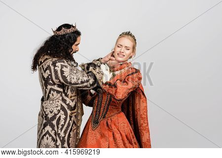 Hispanic King In Medieval Clothing Choking Queen In Crown On White.