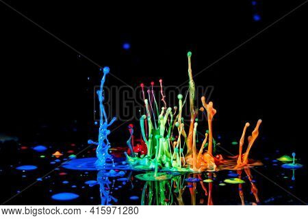 Abstract splash of color ink on black background