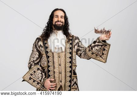 Pleased Hispanic King In Medieval Clothing Holding Golden Crown While Looking At Camera Isolated On