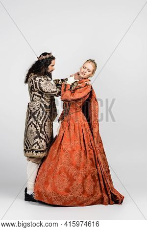 Full Length Of Hispanic King In Medieval Clothing Choking Queen In Crown On White.