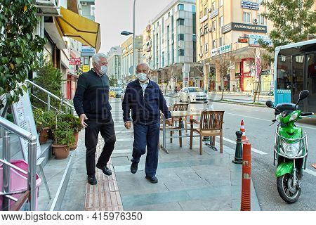 Antalya, Turkey - March 19, 2021: Two Elderly People Wear Protective Face Masks While On City Street